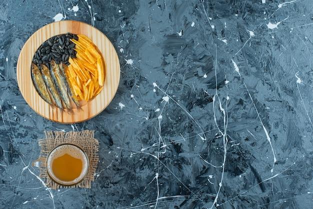 Un bicchiere di birra sulla consistenza e antipasti sul piatto di legno, su sfondo blu.