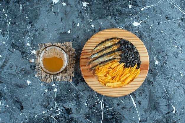 Un bicchiere di birra sulla trama e antipasti sul piatto di legno sul blu.