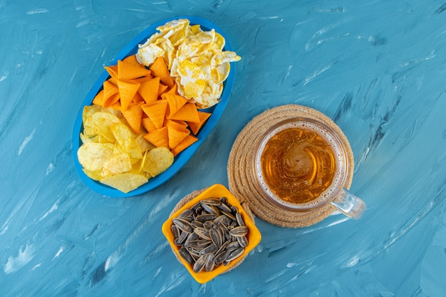 Glass of beer on a trivet next to various chips in a wooden plate , on the blue surface.