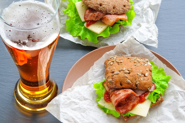 Glass of beer and two burger-like sandwiches with lettuce, bacon, cheese, ketchup on paper, black slate stone