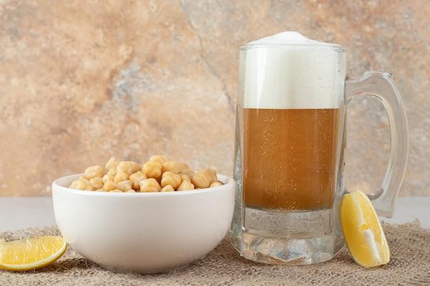 Bicchiere di birra con una ciotola di piselli e fette di limone sul tavolo