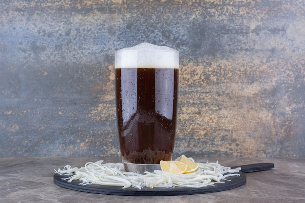 Glass of beer with cheese and lemons on dark board. high quality photo