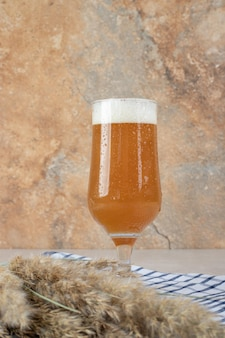 Glass of beer with ears of wheat on tablecloth