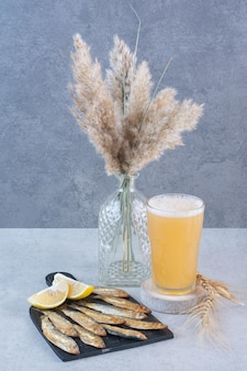 A glass of beer with fish and sliced lemon