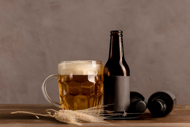Glass of beer with foam and brown bottles of beer on wooden table