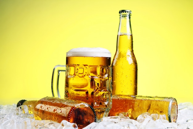 Glass of beer with foam on yellow background