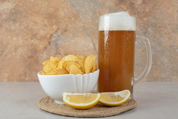 Bicchiere di birra con fette di limone e ciotola di patatine sul tavolo di pietra