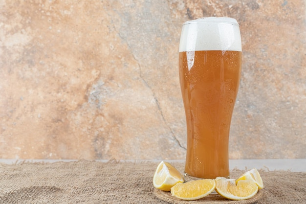 Glass of beer with lemon slices on burlap.