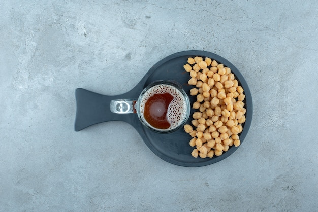 A glass of beer with peas on dark cutting board. high quality photo