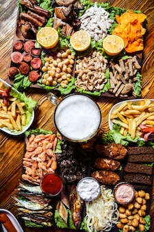 A glass of beer with various snacks for it on the table