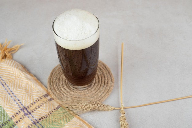 Glass of beer with wheat on stone surface