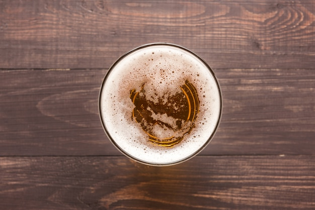 Glass of beer on a wooden background. top view