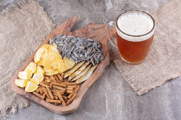 Glass of beer and wooden board of snacks. high quality photo