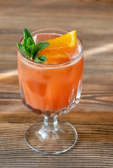 Glass of belmont breeze cocktail garnished with orange slice and fresh mint