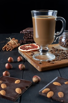 Glass of black coffee with milk with chocolate, hazelnuts, cinnamon sticks and slices of dried grapefruit