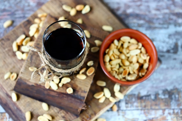 A glass of black soda drink and peanuts. salted peanuts in a glass with coke. american food.