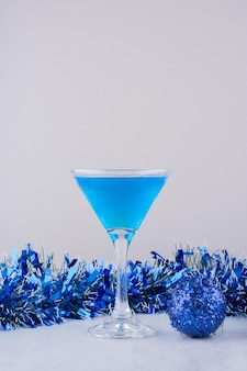 Glass of blue cocktail next to blue christmas decorations on white surface