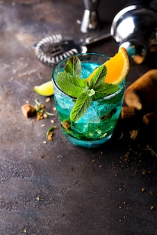Glass of blue lagoon cocktail decorated on a dark concrete background