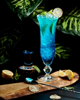 Glass of blue lagoon garnished with lime slices