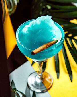 Glass of blue lagoon with ice shaving and cinnamon stick