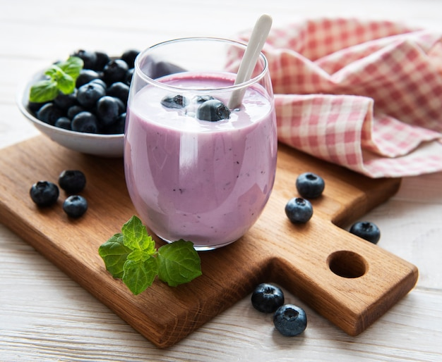 Glass of blueberry yogurt with blueberries on a old wooden background.