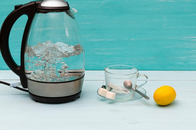 Glass boiling electric kettle on a wooden table.