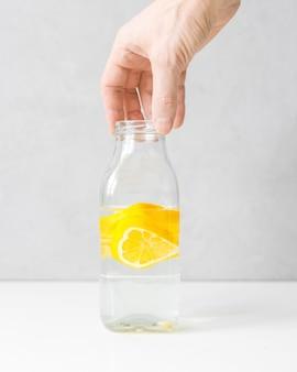 明るい背景に水とレモンとガラス瓶とガラスのゴブレット。レモネード、レモンジュース、柑橘類、オレンジ、ビタミン、ダイエット、デトックス、クレンジング、スムージー、新鮮な朝、水