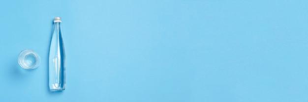 Стеклянная бутылка и стакан с чистой водой на синем пространстве. понятие здоровья и красоты, водный баланс, жажда, жара, лето