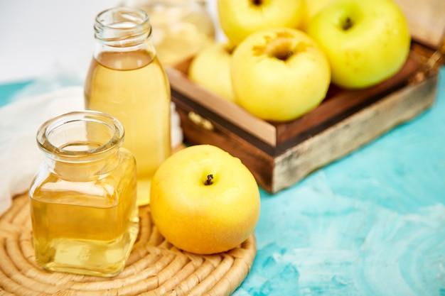 Glass bottle of apple organic vinegar on blue.