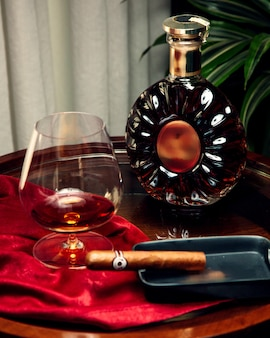 A glass and bottle of cognac and sigar