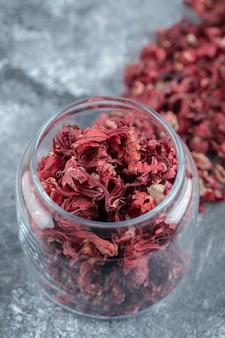Bottiglia di vetro di petali di fiori secchi sul tavolo di marmo.