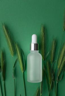緑のテーブルにガラス瓶の必須コラーゲンアンチエイジングセラム、ビタミンaおよびビタミンe