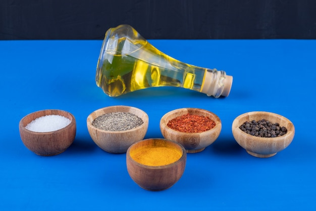 Bottiglia di vetro di olio extra vergine e spezie varie su superficie blu