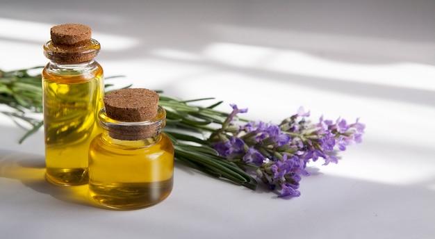 Стеклянная бутылка наполнена маслом лаванды. натуральная косметика, концепция фитотерапии