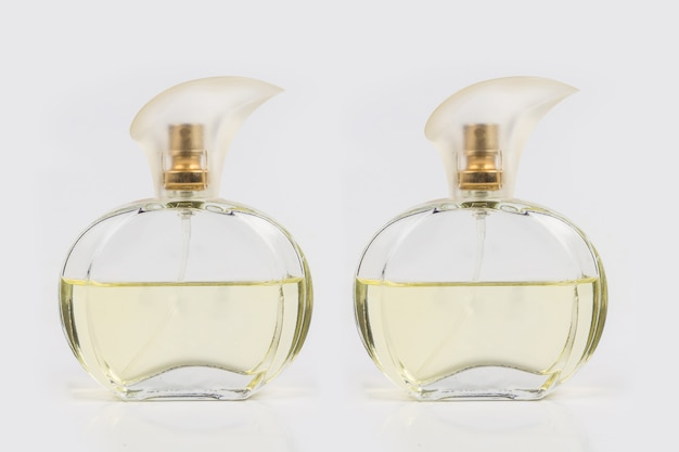 Glass bottle filled with perfume on white
