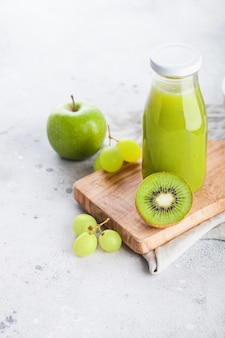 Glass bottle of fresh smoothie juice with organic green toned fruit on stone kitchen. apple, kiwi and grapes