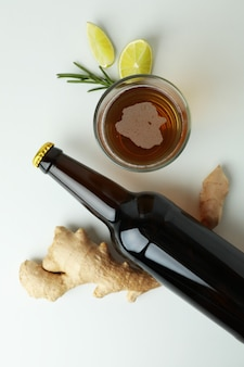 Glass and bottle of ginger beer, and ingredients on white
