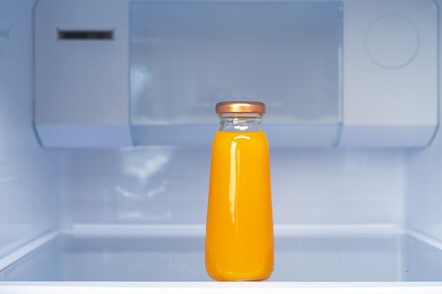 Glass bottle of juice on a fridge shelf