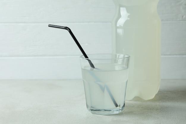 Glass and bottle of lemonade against white wooden surface