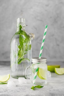 Glass bottle and lemonade jar with cold lemonade with fresh mint leaves and lime with ice cubes on grey concrete