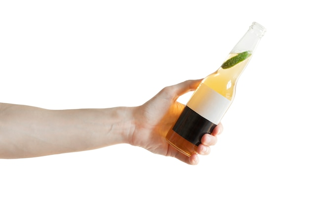 A glass bottle of light beer with a slice of lime inside the bottle in men's hand isolated on white