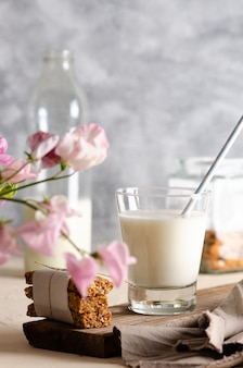 A glass and a bottle of milk cereal bars some almonds in a jar with pink fowers