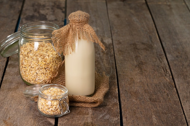 Glass bottle of milk and oat flakes in jar on old wooden table