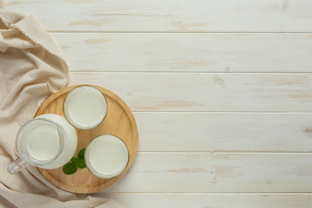 Glass and bottle of milk on white wooden surface
