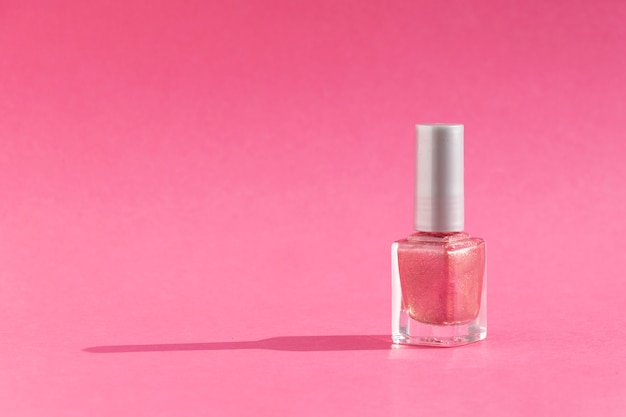 Glass bottle of nail polish on pink background