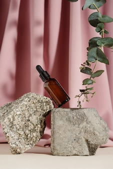 Glass bottle of natural oil or serum on stone bricks with eucalyptus branch