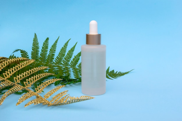 Glass bottle of natural oil with golden fern palm leaves. cosmetic skincare products, modern concept of organic beauty trend.