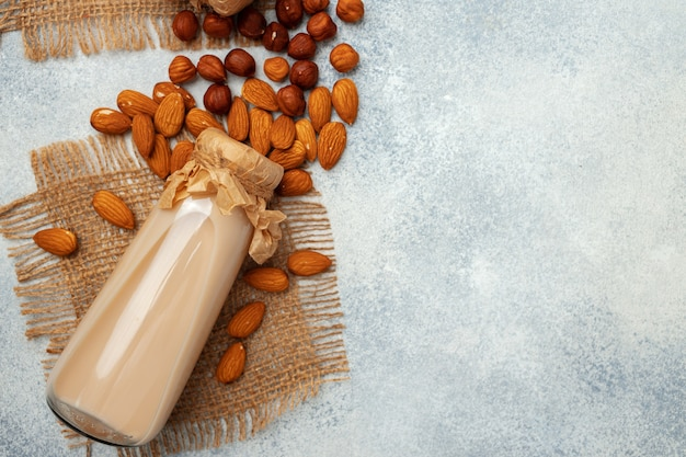 Glass bottle of nut milk and nuts on wooden desk