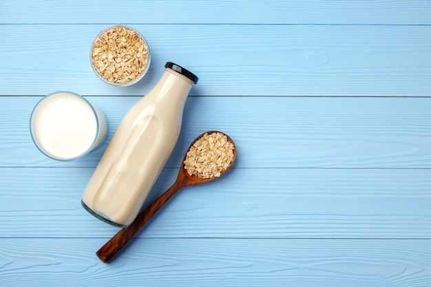 Glass bottle of oat milk and oat flakes in bowl, top view