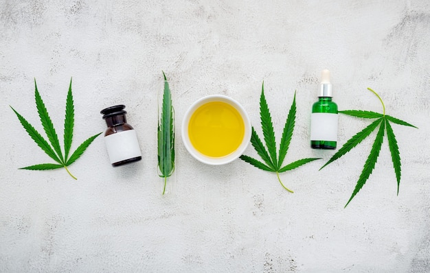 大麻油と麻の葉のガラス瓶がコンクリートの上に設置されました。